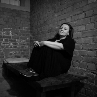 A woman in her late forties sits on a wooden bed in a room with bare brick walls. She is wearing a long black dress and trainers, and has her legs pulled up, holding her knees.